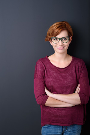 Confident smiling attractive young redhead woman with folded arms wearing glasses standing against a dark studio background with copyspace