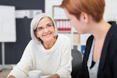 amigas conversando: Gray mayor cabelludo negocios con la expresión facial feliz mira a su colega dentro de la oficina.