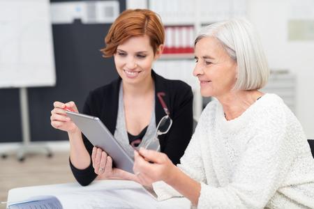 Junge Bürofrau Lehre ihr ältere Kollegin auf wie zu benutzen Tablet Computer innerhalb des Arbeitsplatzes.