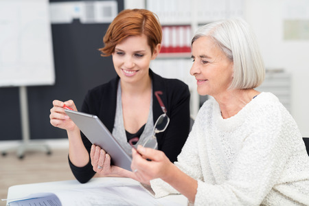 workplace: Young Office Woman Teaching her Senior Female Colleague on how to Use Tablet Computer Inside the Workplace. Stock Photo