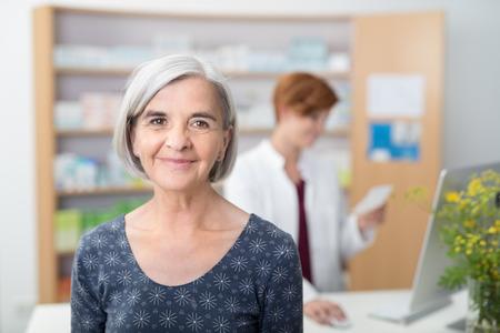 Lachende oudere patiënt in een apotheek, hoofd en schouders voor de camera met een jonge vrouwelijke apotheker werkzaam zijn in de achtergrond