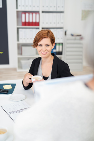 colleagues: Pretty Young Office Woman with a Cup of Coffee Looking at her Colleague Inside Workplace. Stock Photo