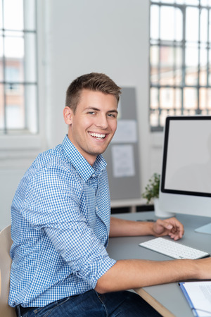 Happy handsome young businessman at work in the office sitting at his desk turning to give the camera a lovely friendly warm smile