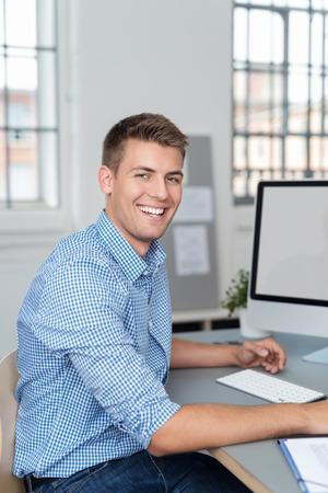 monitor de computadora: Feliz joven apuesto hombre de negocios en el trabajo en la oficina sentado en su escritorio de pasar a dar a la cámara un precioso cálida sonrisa Foto de archivo