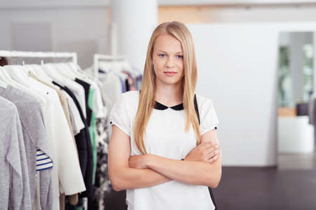 saleslady: Half Body Shot of a Confident Blond Young Woman Looking at the Camera with Arms Crossing on her Chest Inside the Clothing Store. Stock Photo