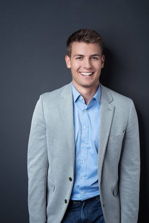 young man portrait: Half Body Shot of a Cheerful Handsome Young Businessman Standing Against Gray Wall Background and Smiling at the Camera.