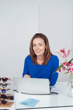saleslady: Pretty Young Woman Leaning Against Cashier Counter with Laptop in a Fashion Store and Smiling at the Camera