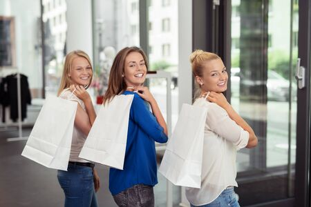 package: Three Pretty Girl Friends Holding White Shopping Bags Over their Shoulders and Smiling at the Camera. Stock Photo
