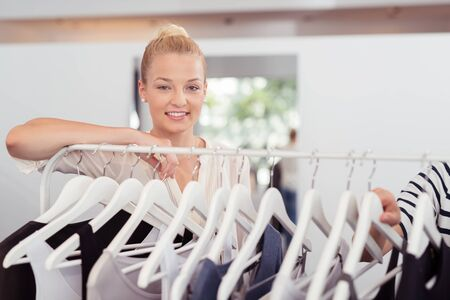 hanged woman: Attractive Young Woman Leaning Against Clothing Rail with Hanged Clothes Inside Fashion Store. Stock Photo