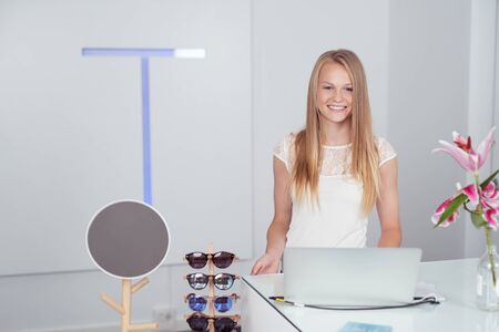 saleslady: Pretty Blond Girl Standing at Cashier Counter with Laptop Computer Inside the Fashion Store, Smiling at the Camera.