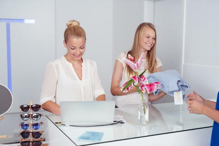 saleslady: Cheerful Pretty Blond Girls at Cashier Counter Inside a Fashion Store.