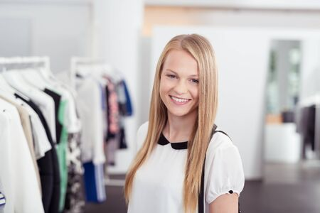 blond girl: Half Body Shot of a Pretty Blond Girl Smiling at the Camera Inside the Clothing Store.