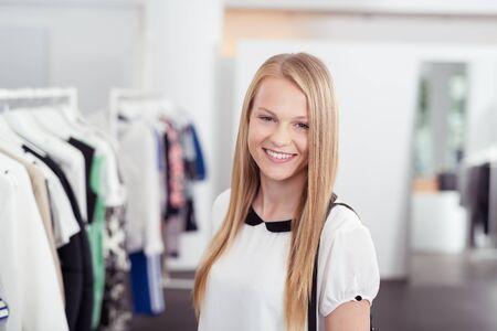 tienda de ropa: La mitad de tiro del cuerpo de una muchacha bastante rubia que sonríe en la cámara dentro de la tienda de ropa. Foto de archivo