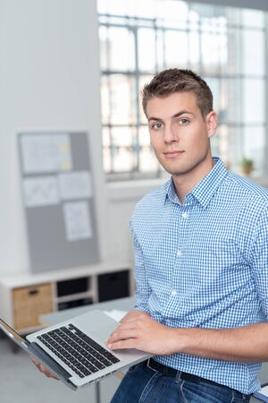 shirtsleeves: Half Body Shot of a Handsome Young Businessman Holding his Laptop Computer and Looking at Camera Inside the Office.