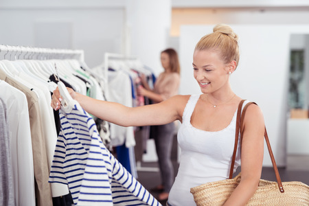 Happy young blond woman shopping for clothes holding up a striped top in a fashion boutique with a smile Stock Photo