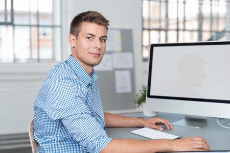 shirtsleeves: Handsome Young Businessman Sitting at his Desk with Blank Screen Computer, Smiling at the Camera. Stock Photo