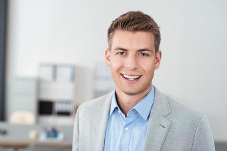 profesiones: Close up amistoso Hombre de negocios apuesto joven dentro de la Oficina, sonriendo a la cámara.
