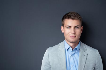 ハンサムな実業家は微笑みを左にコピー スペースを持つ灰色壁背景に対してカメラを閉じます。