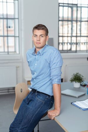 young businessman: Handsome Young Businessman Leaning his Back Against his Table Inside the Office and Looking at the Camera. Stock Photo