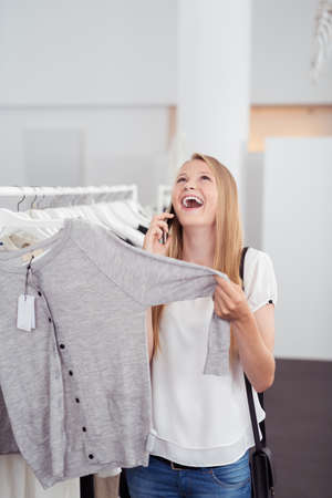 laughing out loud: Young Woman Laughing Out Loud While Talking To Someone on Mobile Phone inside the Clothing Store Stock Photo