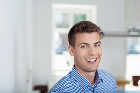 enterprising: Close up Cheerful Handsome Young Businessman Smiling at the Camera Inside the Office. Stock Photo
