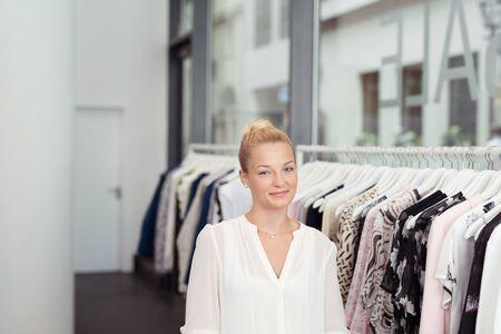 tienda de ropa: La mitad Shot cuerpo de una atractiva mujer rubia en un almacén de ropa sonríe en la cámara.