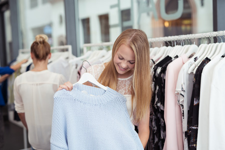 clothing store: Happy Pretty Blond Lady Shopping for an Affordable Nice Trendy Dress Inside a Clothing Store.