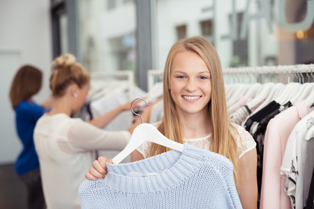 blond girl: Close up Pretty Blond Girl Holding a Hanged Shirt Inside a Clothing Store and Smiling at the Camera