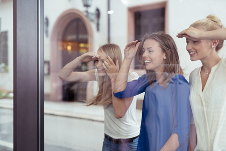 Three Happy Girl Friends at the Street Looking What is Inside the Store Through Glass Window.