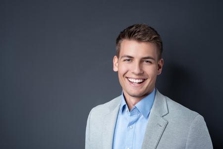 portrét: S úsměvem pohledný temperamentní šťastný mladý muž v saku představuje proti tmavému pozadí s copy-space, Hlava a ramena portrét