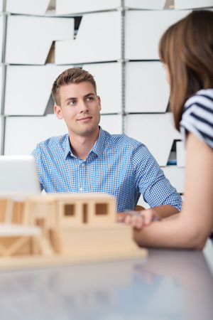 scale model: Inquisitive Young Businessman Listening to his Female Supervisor Talking While having a Meeting In the Office.