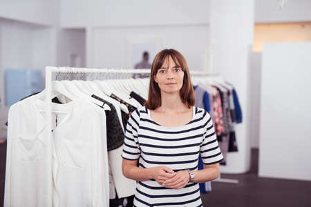 saleslady: Half Body Shot of an Adult Woman Inside a Clothing Store Looking Straight at the Camera Stock Photo