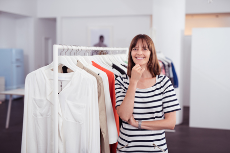 clothing shop: Half Body Shot of a Happy Adult Woman inside a Clothing Shop, Smiling at the Camera with One Hand on her Chin. Stock Photo