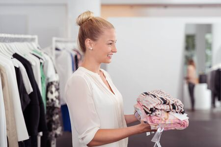 sale shop: Half Body Side View Shot of a Pretty Young Woman Holding a Pile of Clothes to Buy Inside the Clothing Store Stock Photo