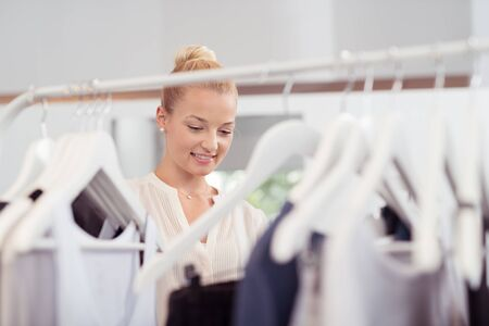 clothing store: Attractive Young Woman Behind Clothing Rail Looking for Clothes Inside Fashion Store. Stock Photo
