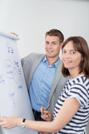job qualifications: Two Young Businesspeople in a Brainstorming Session, Smiling at the Camera while Making a Conceptual Business Diagram on White Poster Paper. Stock Photo