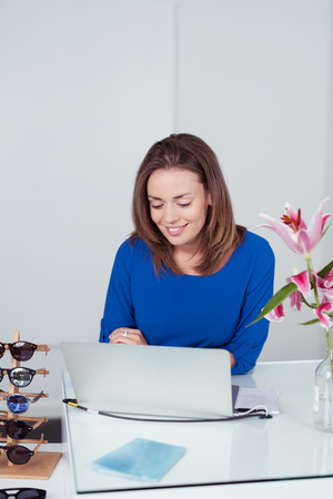 saleslady: Attractive Young Woman Checking Out a Laptop Computer Inside a Fashion Store with Happy Facial Expression. Stock Photo
