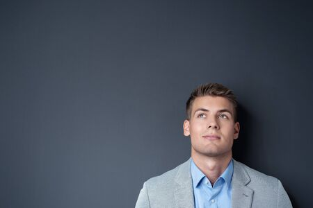 contemplative: Pensive handsome young man posing against a dark background with copyspace looking up into the air with a contemplative expression, head and shoulders view