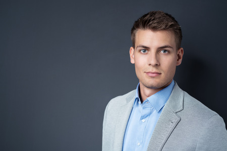 determined: Handsome young businessman looking at the camera with a serious expression against a blackboard with copyspace, head and shoulders view Stock Photo