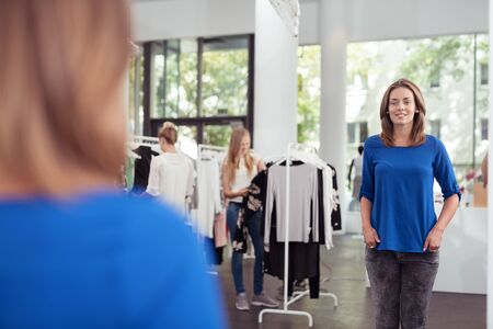 DEPARTMENT: Pretty Young Woman Inside Clothing Store Looking at her Reflection on the Wall Mirror