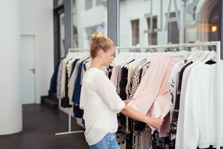 retail: Stylish Blond Girl Looking at the Clothes Hanging on Rail inside the Clothing Store Stock Photo