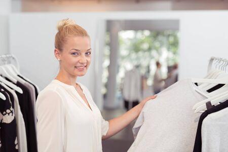 ahorcada: Toma la mitad del cuerpo de una mujer rubia de la mujer dentro de una tienda de ropa, mostrando un vestido blanco colgado en Rail en la cámara. Foto de archivo