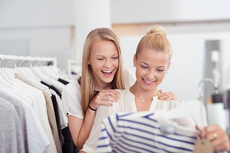 clothing store: Happy Girl Friends Looking at the Quality of a Casual Shirt inside the Clothing Store. Stock Photo