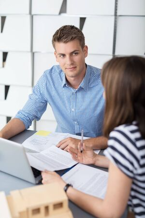 one on one meeting: Handsome Young Businessman Listening to his Female Colleague Talking While Having a One on One Meeting Inside the Office.