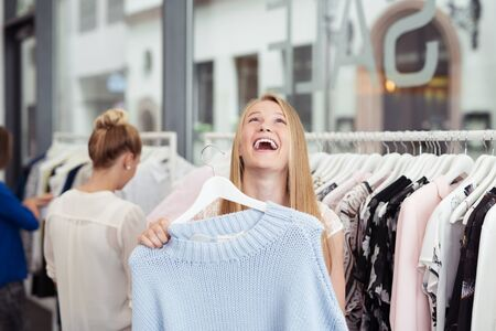 hanged woman: Happy Young Woman Laughing Out Loud While Holding a Hanged Shirt Inside the Clothing Store.