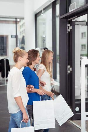 out door: Three young women shoppers leaving a department store or boutique carrying plain white shopping bags with copyspace for your advertising