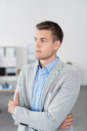 one people: Half Body Shot of a Pensive Young Handsome Businessman Looking Into the Distance with Arms Crossed. Stock Photo