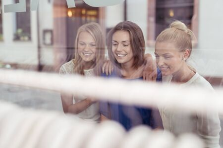 woman shop: Three Happy Girls Looking at the Clothes on Rail inside a Fashion Store Through Glass Window. Stock Photo