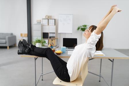 mujer sentada: Pensativo mujer Oficina Estirar su cuerpo mientras se sienta en su silla con las piernas sobre el escritorio. Foto de archivo