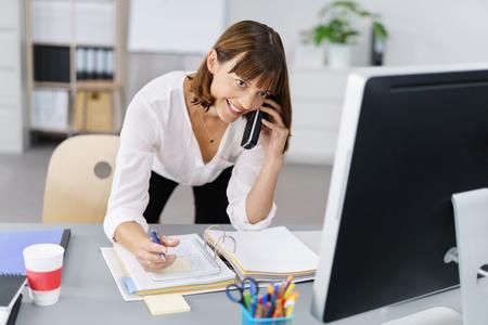 persona escribiendo: Empresaria ocupada que toma una llamada de teléfono mientras se inclina sobre la información lectura escritorio en su monitor de la computadora de escritorio con una sonrisa feliz